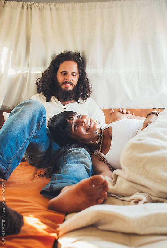 On The Road - Heterosexual Hippie Couple Lying and Smiling in Camper Van by Julien L. Balmer for Stocksy United