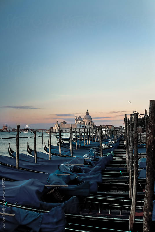 Venetian gondolas with the basilica santa maria della salute in the back by Leander Nardin for Stocksy United