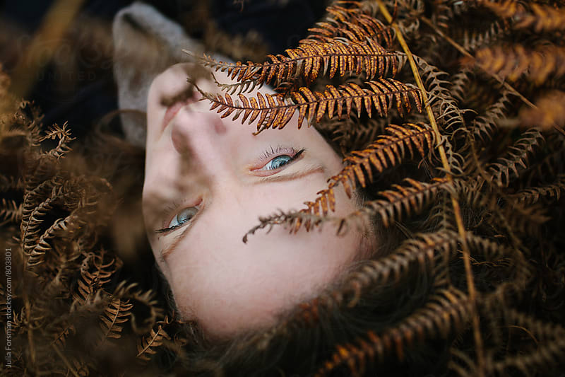 Face of pale woman lying on ground among autumnal foliage by Julia Forsman for Stocksy United