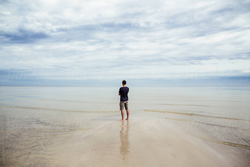 Man standing at shore looking to the horizon by Lior + Lone for Stocksy United