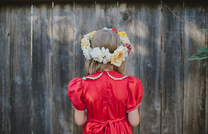 young girl with red dress on wearing a homemade floral crown by Kristin Rogers Photography for Stocksy United