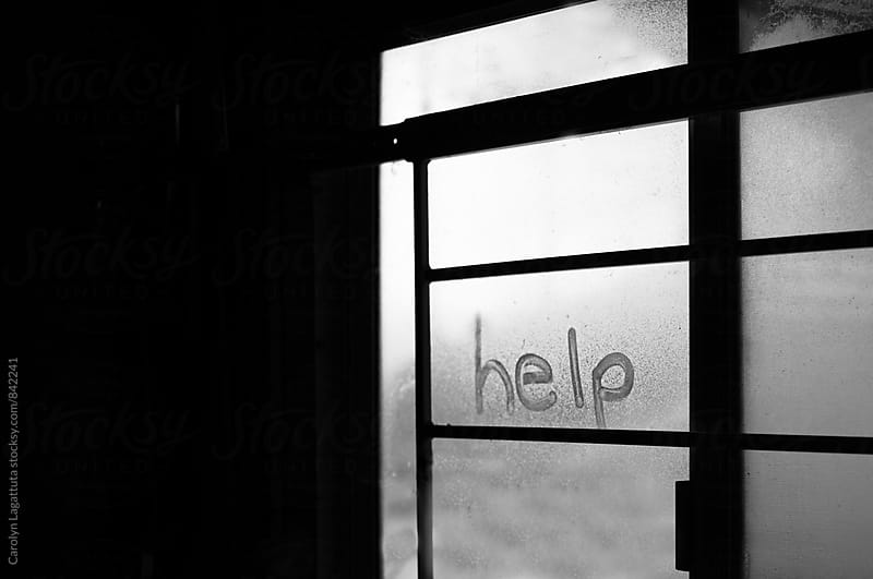 Help written in the dust of a window with bars on it by Carolyn Lagattuta for Stocksy United