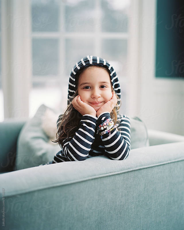 Portrait of a beautiful young girl sitting in a chair with a hoodie by Jakob for Stocksy United