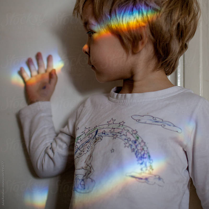 Child wearing and holding rainbows indoors. by Julia Forsman for Stocksy United
