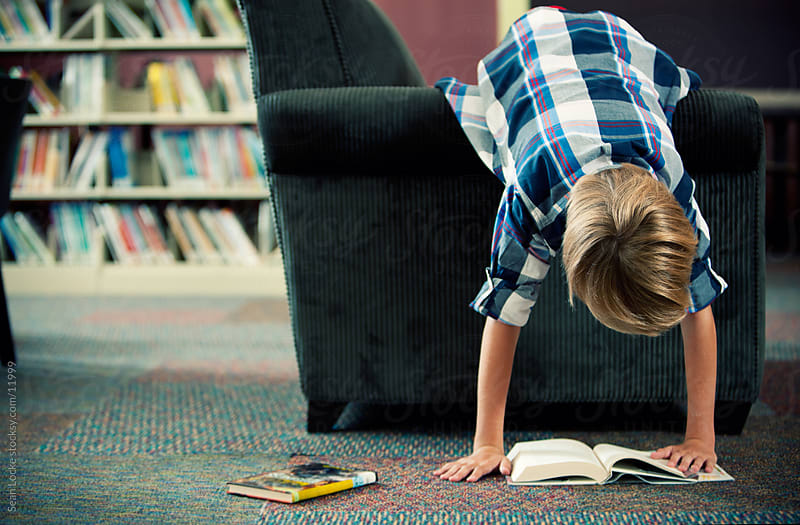 Library: Boy Engrossed with Reading Books by Sean Locke for Stocksy United
