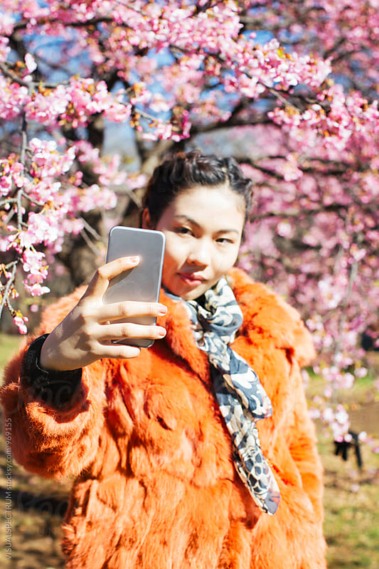 Pretty Young Japanese Woman Taking Selfie in Front of Blossoming Sakura Tree by Julien L. Balmer for Stocksy United