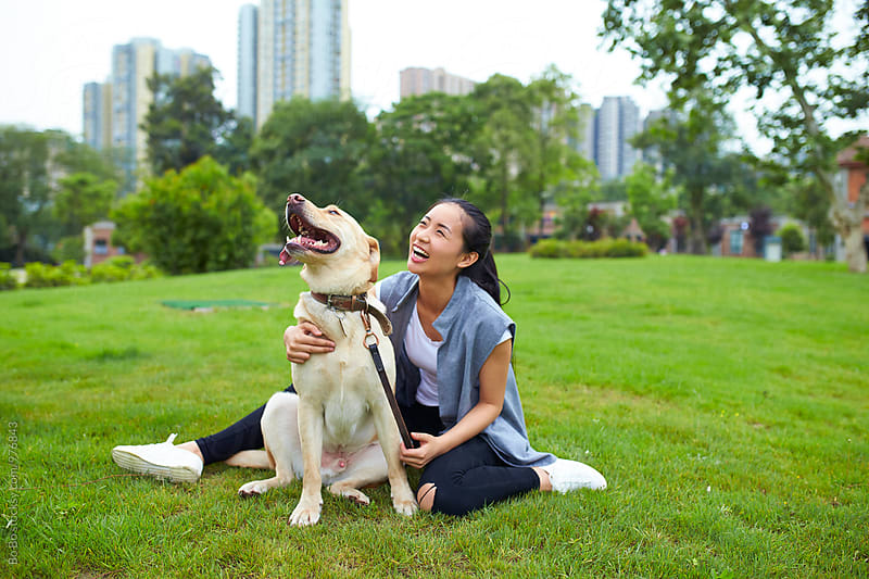 young asian woman with her dog outdoor in the park by Bo Bo for Stocksy United