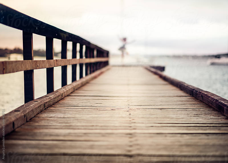 A wooden dock above a river on a cloudy day by Angela Lumsden for Stocksy United