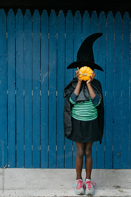Black girl holding a pumpkin in Haloween costume by Gabriel (Gabi) Bucataru for Stocksy United