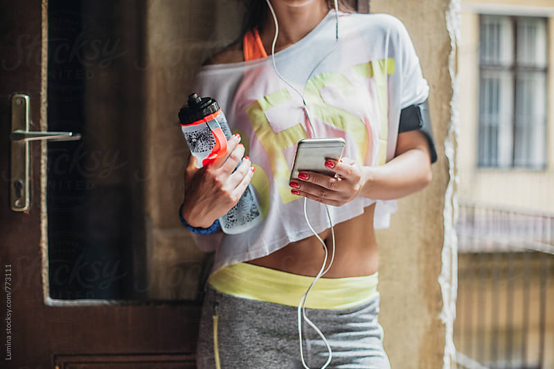 Woman in Fitness Clothes Using a Mobile Phone by Lumina for Stocksy United