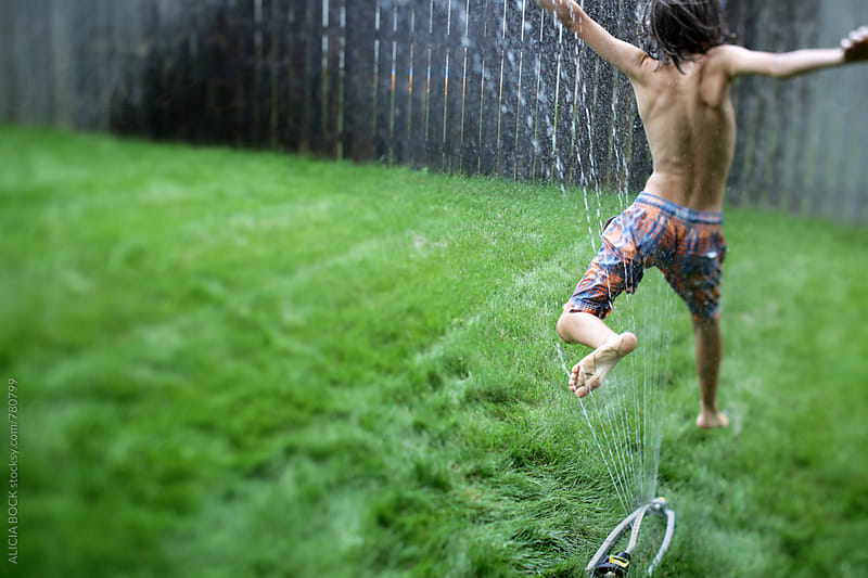 A Boy Jumping Through A Sprinkler In His Yard On A Hot Summer Day by ALICIA BOCK for Stocksy United