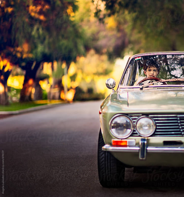 Boy in driver's seat of an old car by Angela Lumsden for Stocksy United