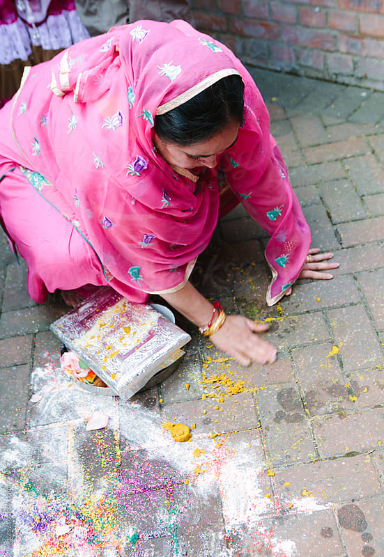 Mother of the groom collects the Rangoli during Mayian ceremony of Sikh wedding by kkgas for Stocksy United
