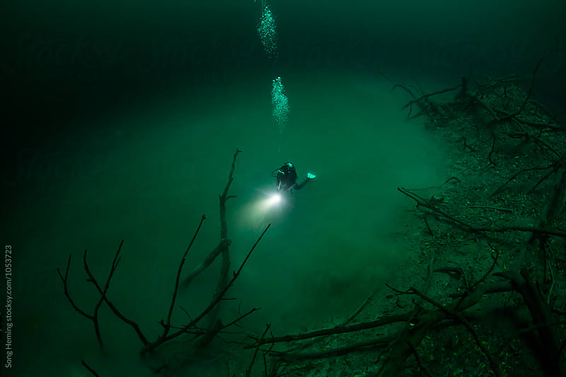 A scuba diver swimming in Mexico's  Cenote Angelita by Song Heming for Stocksy United