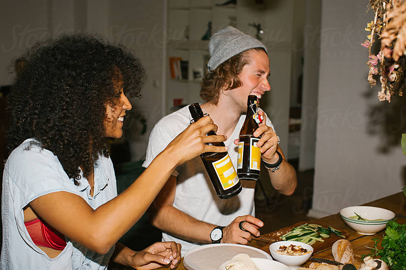Snapshot of Two Friends Toasting With Beer and Having a Laugh by Julien L. Balmer for Stocksy United