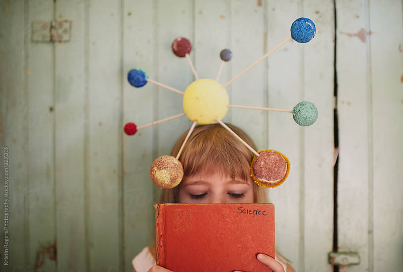 Young girl with playing with her homemade solar system craft by Kristin Rogers Photography for Stocksy United