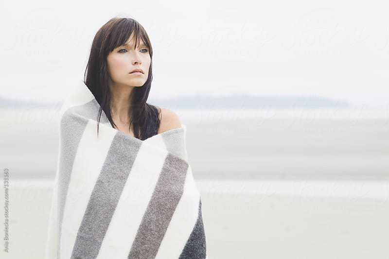 A portrait of a young brunette looking into the distance wrapping herself up with a blanket by Ania Boniecka for Stocksy United