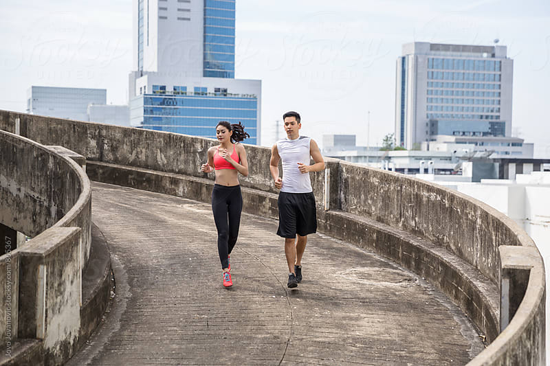 A handsome young couple jogging together in an urban environment  by Jovo Jovanovic for Stocksy United