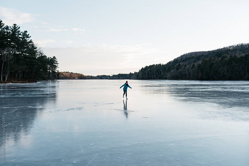 young woman skating alone on a lake by Léa Jones for Stocksy United