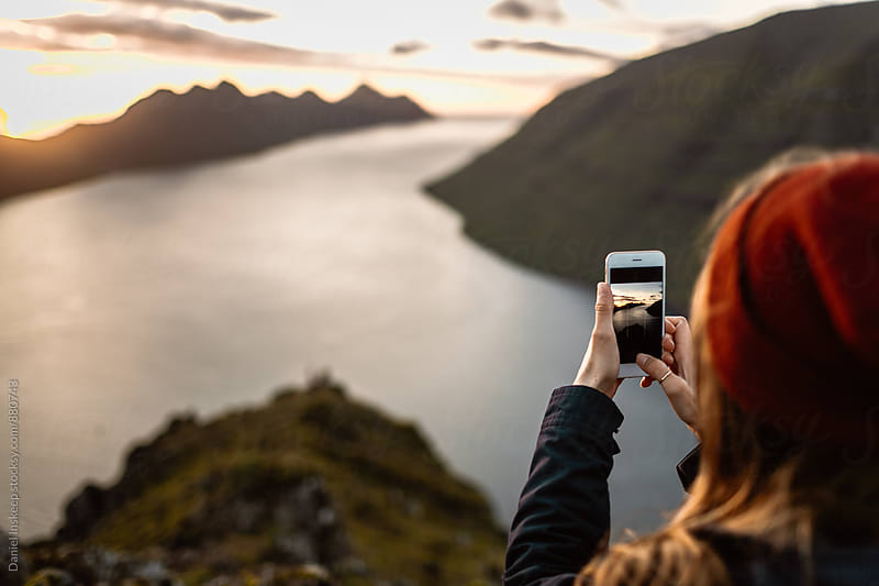 Woman Taking an iPhone Photo Atop a Mountain by Daniel Inskeep for Stocksy United