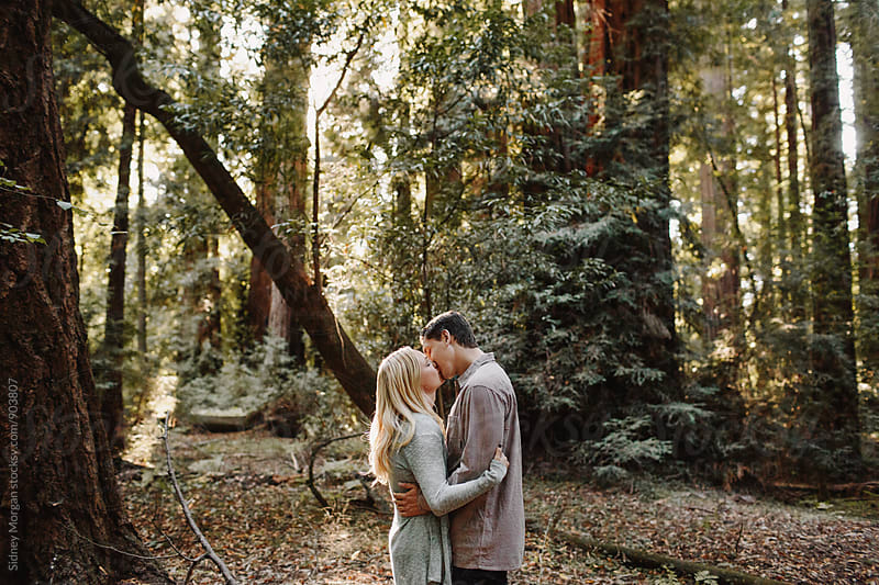 Couple Kissing in Front of Redwoods by Sidney Morgan for Stocksy United