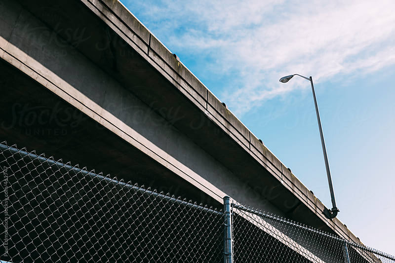 Highway overpass and fence in foreground by Paul Edmondson for Stocksy United
