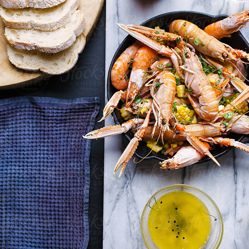 A seafood meal served in a skillet with garlic butter and bread. by Darren Muir for Stocksy United