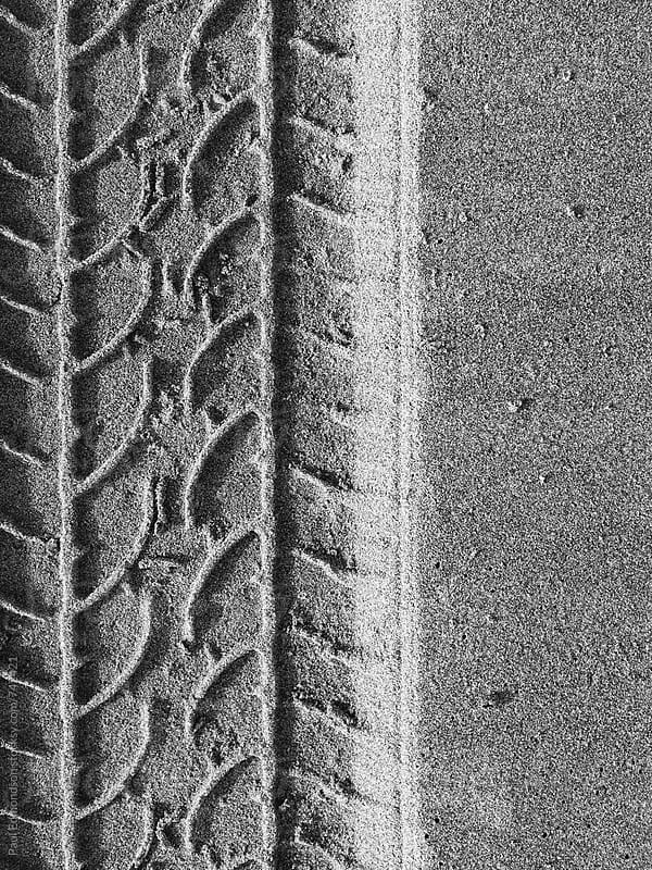 Close up of tire tracks on beach by Paul Edmondson for Stocksy United