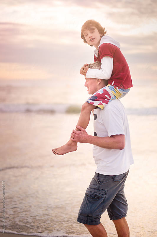 Boy carried on his father's shoulders at beach at sunset by Angela Lumsden for Stocksy United