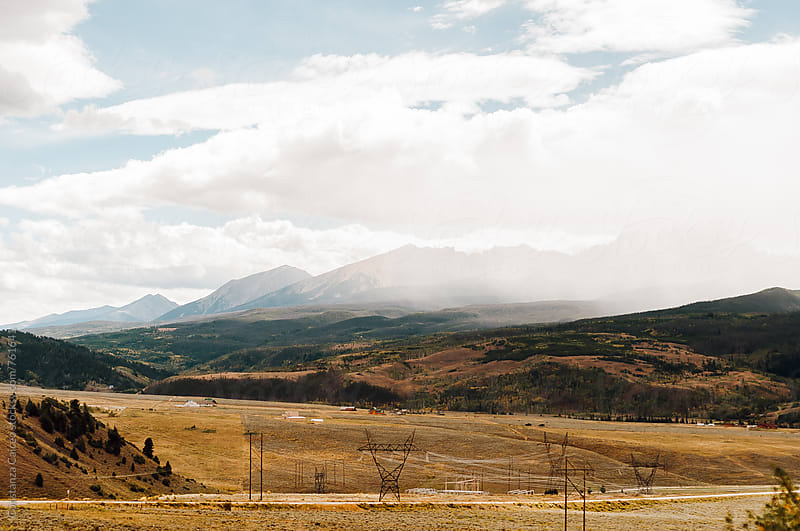 View of a back country road on an open land on a sunny morning day with mountains in the background  by Constanza Caiceo for Stocksy United