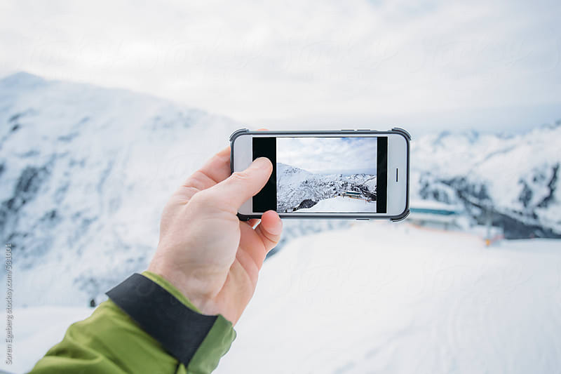 Man photographing beautyfull mountains landscape with a  mobile smart phone by Soren Egeberg for Stocksy United