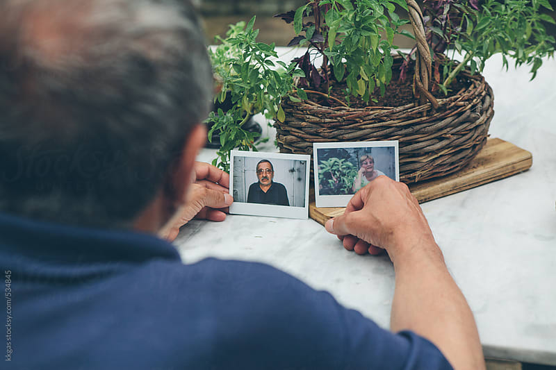 Senior man looking at instant photos of himself and his wife by kkgas for Stocksy United