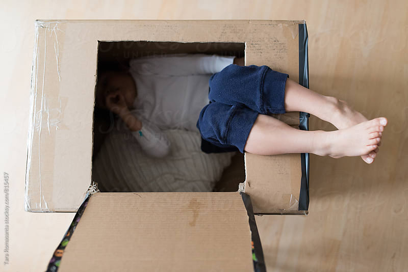 child in a box, view from above by Tara Romasanta for Stocksy United