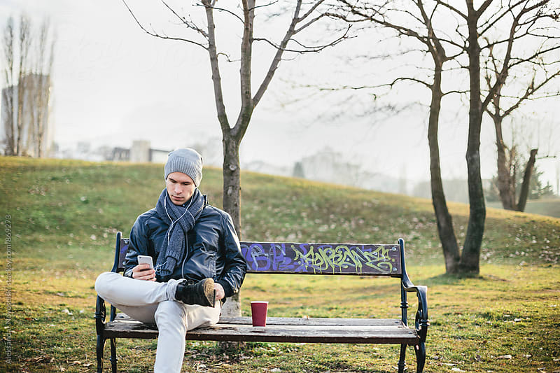 Young man using his smartphone, while sitting on a bench and drinking coffee by Aleksandar Novoselski for Stocksy United