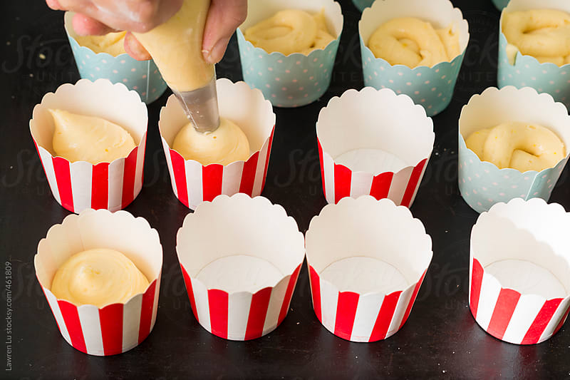 Young woman hands piping cake mixture into molds for making muffin. by Lawren Lu for Stocksy United