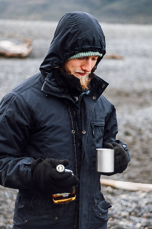 Young man drinking fine whisky on a cold day in the chilean Patagonia by Constanza Caiceo for Stocksy United