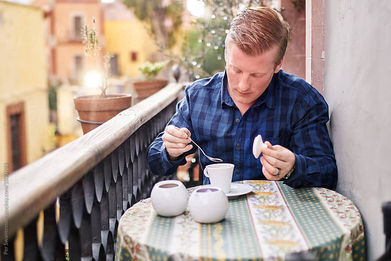 Man drinking coffee on a quaint balcony by Per Swantesson for Stocksy United