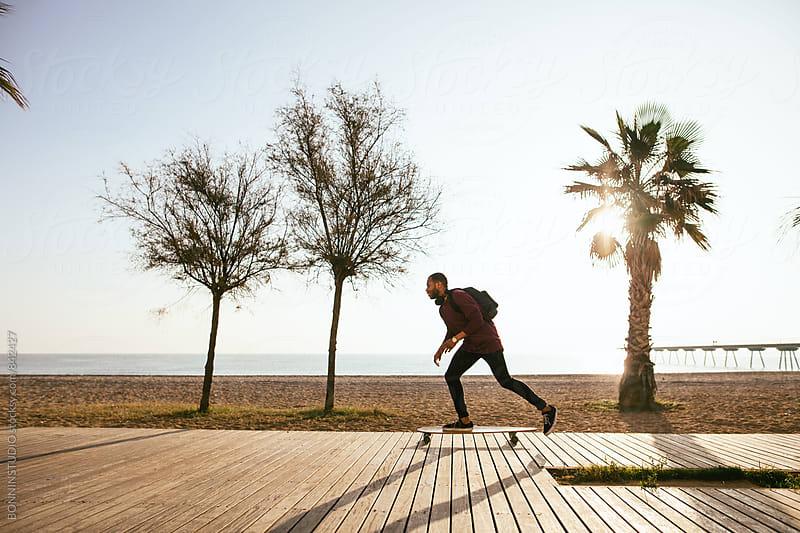 Man riding on longboard on beach promenade. by BONNINSTUDIO for Stocksy United