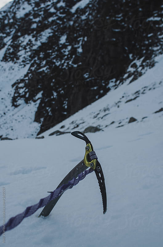 Ice Axe in the Snow by Neil Warburton for Stocksy United