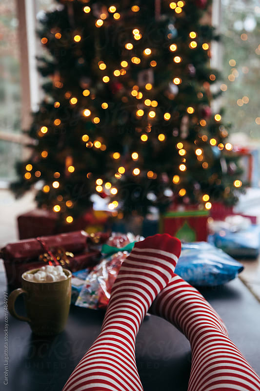 Person in striped knee highs in front of the Christmas tree by Carolyn Lagattuta for Stocksy United