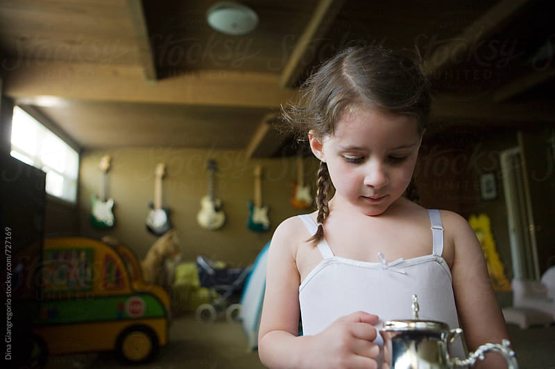 Little Girl Holding Tea Pot In Cool Room by Dina Giangregorio for Stocksy United