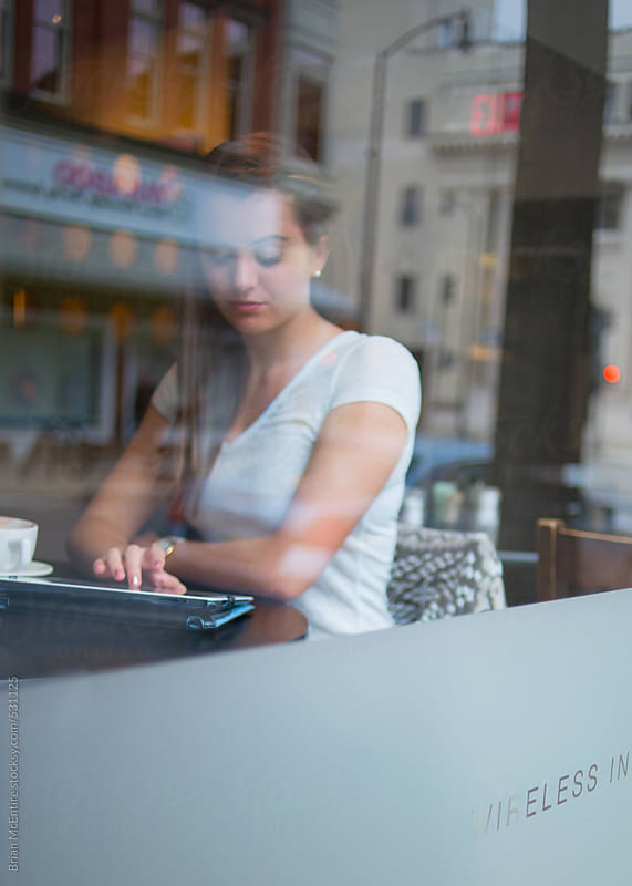 Young woman using tablet seen through cafe window by Brian McEntire for Stocksy United