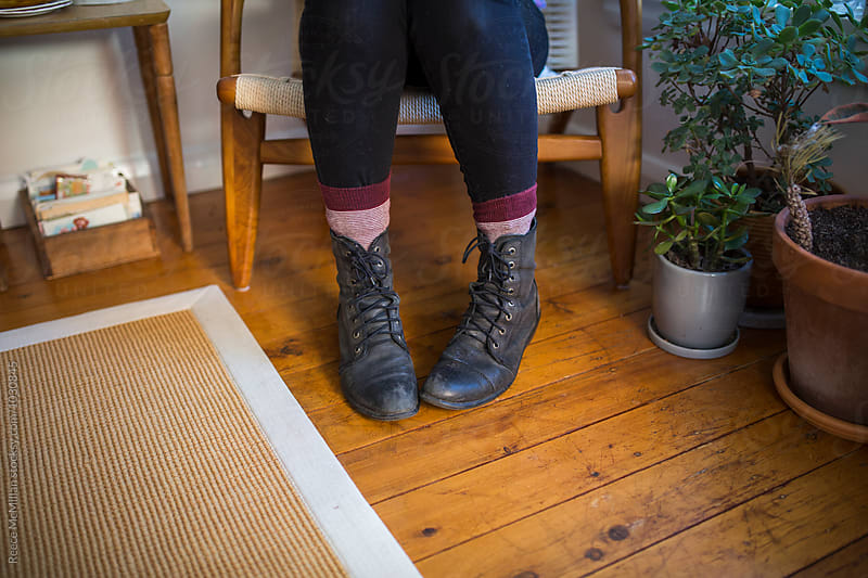 A girls feet in combat boots at home by Reece McMillan for Stocksy United