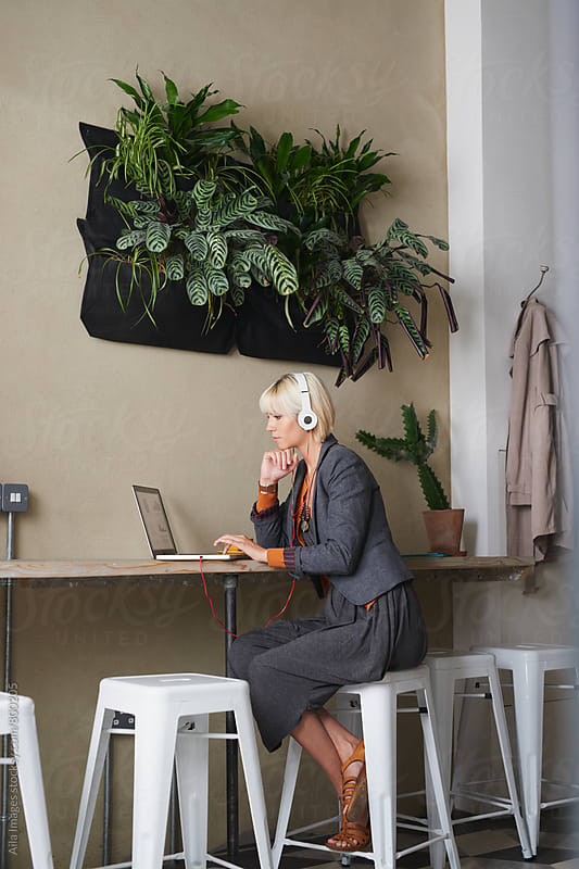 Young attractive sophisticated blonde woman in cafe worksing on laptop listening to music on white headphones enjoying hot fresh coffee in yellow cup by Aila Images for Stocksy United