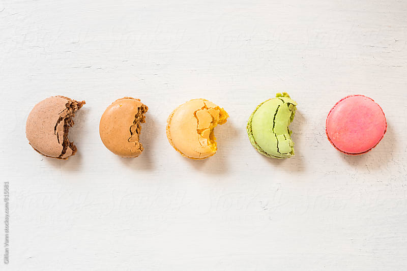 pastel macarons with bites by Gillian Vann for Stocksy United