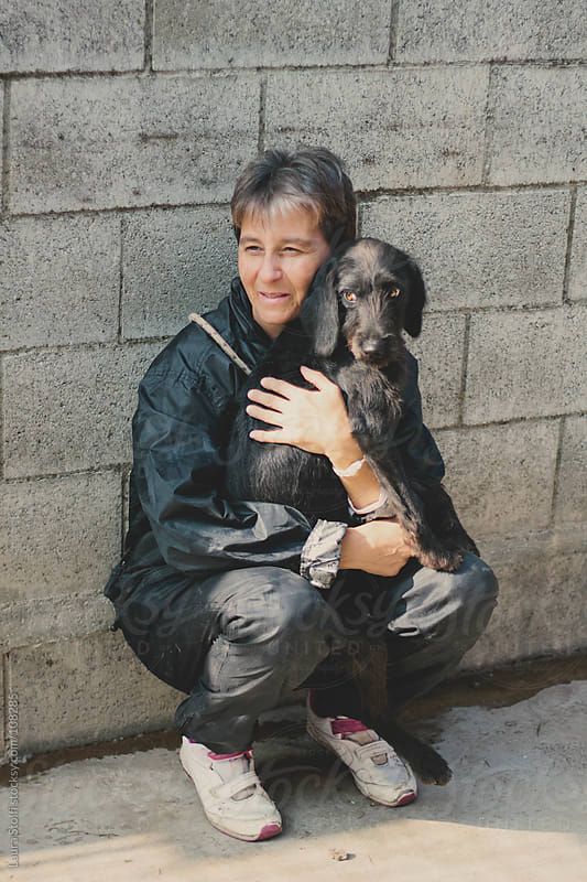 Woman bended on her legs holds a black dog in her arms by Laura Stolfi for Stocksy United