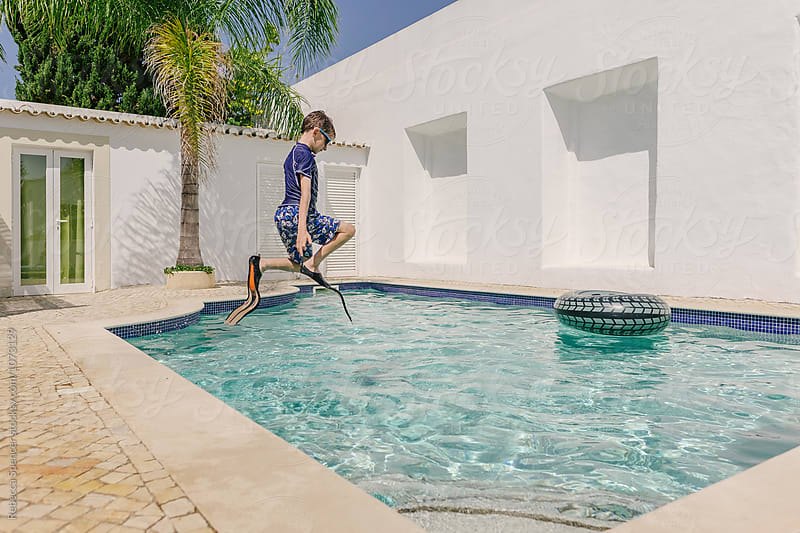 Child photographed mid jump above swimming pool by Rebecca Spencer for Stocksy United