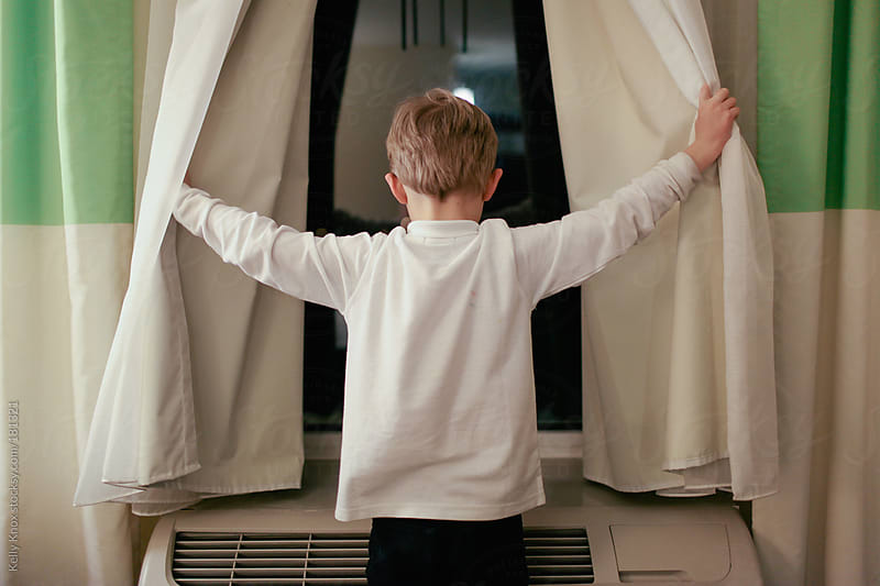 boy looking out of a hotel window by Kelly Knox for Stocksy United