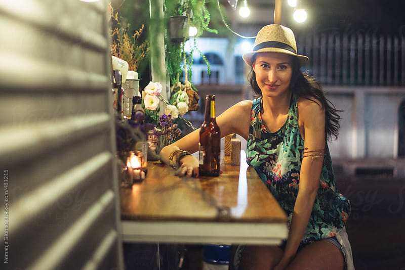 Friendly Young Woman Sitting at the Food Truck Counter With Beer by Nemanja Glumac for Stocksy United