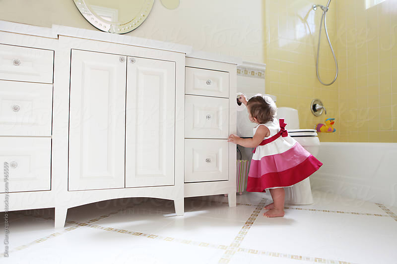 Toddler In Party Dress Reaching For Toilet Paper Roll by Dina Giangregorio for Stocksy United
